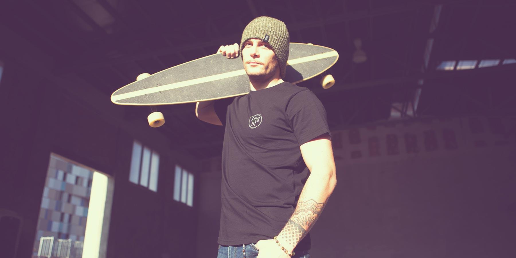 Ragazzo con tavola da skate, t-shirt nera e berretto verde Costa Est