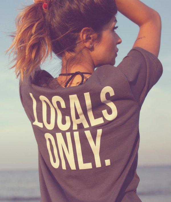 Ragazza in spiaggia con t-shirt grigia con stampa Locals Only sulla schiena