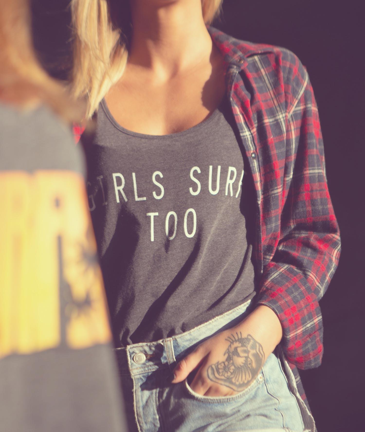 Ragazza con canotta grigia con scritta Girls Surf Too e camicia scozzese