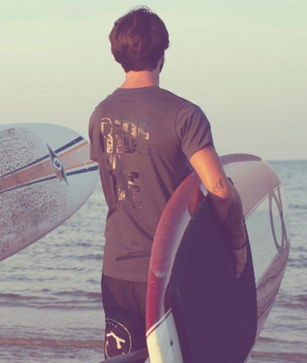 Surfista sulla spiaggia con tavola e t-shirt grigia con stampa Ride or Die Costa Est Beachwear
