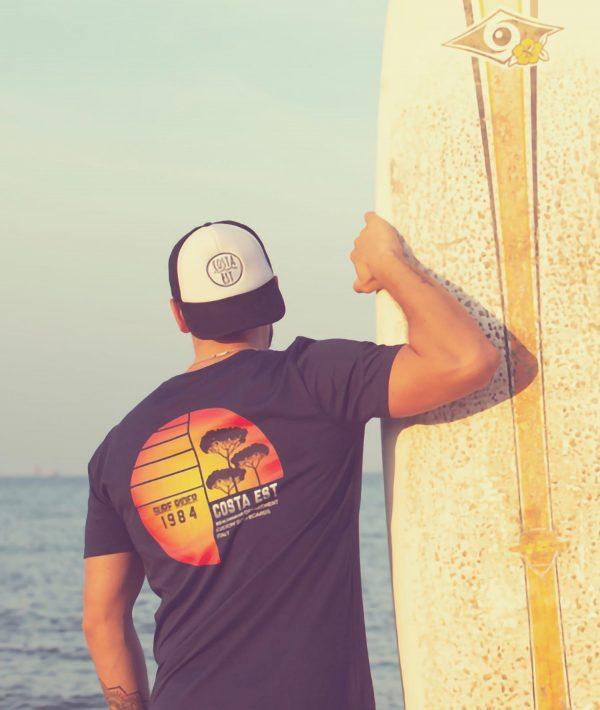 Ragazzo con tavola da surf sulla spiaggia, che indossa la t-shirt blu navy con stampa sulla schiena Surf Rider 1984 Costa Est