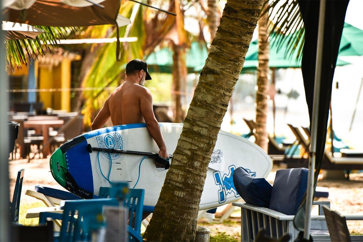 Uomo con tavola da surf sulla spiaggia