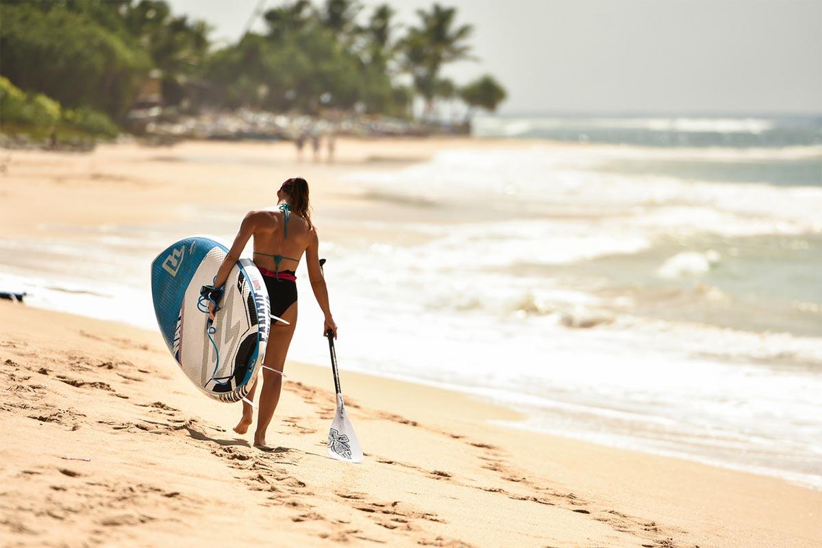 Ragazza con tavola da surf nella spiaggia